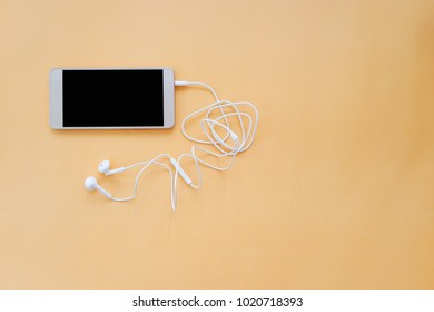 Smartphone and Earphones wit Tangled Cable on Orange Background Top View