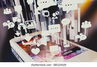 Smartphone emitting holographic social media icons.