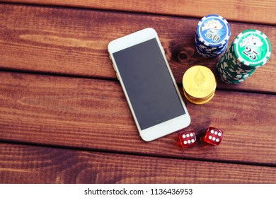 Smartphone, ethereum coins , dice and poker chips. Online casino concept, payment by ethereum.