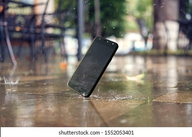 Smartphone falling and crashing on wet ground in the city park on a rainy day. accident with smartphone