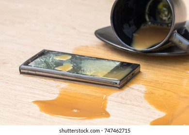 Smartphone falls to the ground with broken and coffee spilled