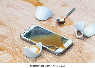 Smartphone falls to the ground with broken and coffee spilled on wooden floor