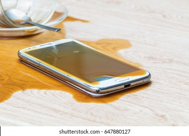 Smartphone falls on ground and broken with coffee spilled on background texture