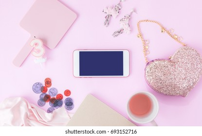 Smartphone with fashion accessories, cracker fancy,coffee mug, and Chocolate gold on pastel pink colors office table Mix for ladies and young girls using smart Phone On table desk in holidays .