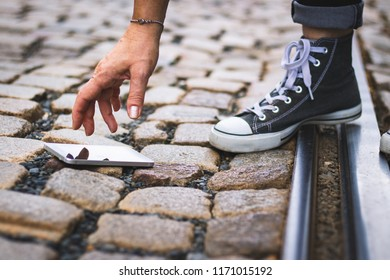 Smartphone fell on a cobbled street, woman lifting a smartphone from a cobblestone street before is tramway arrival. Be careful.
