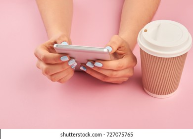 Smartphone in female manicured hands. Hands with manicure holding mobile phone, cardboard cup of coffee, pink background.
