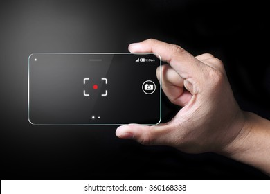 Smartphone and focus point with hand on dark background. Smartphone cameras are approaching the quality of point-and-shoot cameras.