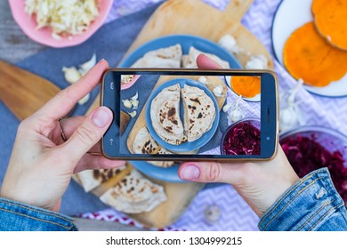 Smartphone food photography. Woman hands holds phone and take photo of dinner or lunch with stuffed garlic naan or fried chapati Indian bread for social media or blogging. Vegetarian, vegan.