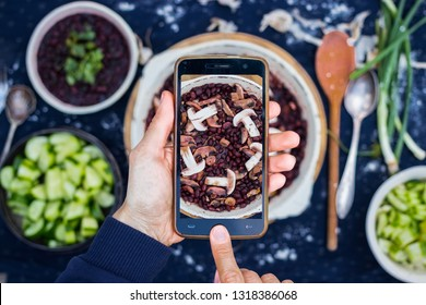 Smartphone food photography. Woman hands take phone food photo. Dinner, table, black dark background. Vegetarian beans with mushrooms healthy lunch. Blogging or social networks style. Top, above view.
