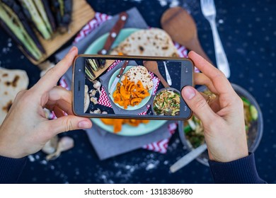 Smartphone food photography. Woman hands take phone food photo. Dinner, pumpkin and bread, table, black dark background. Vegetarian healthy lunch. Blogging or social networks style. Top, above view.