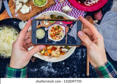 Smartphone food photography. Woman hands take phone food photo. Dinner of baked vegetables, table, black dark background. Vegetarian healthy lunch. Blogging or social networks style. Top, above view.