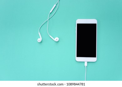 Smartphone Get Plugged in with Earphones on Turquoise Background Top View