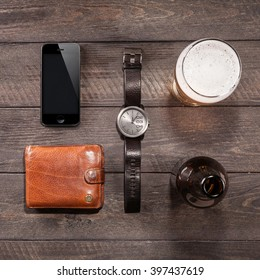 Smartphone and glass of beer near watches on wooden. men's stuff