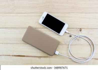 Smartphone with golden powerbank on wood desk.