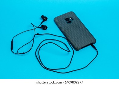 Smartphone in a gray textile case with connected headphones on a blue background