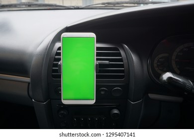 smartphone with green screen (Chroma key) with Car dashboard background.