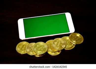 Smartphone with green screen on the side with the bitcoin placed coins