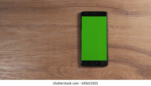 smartphone with green screen over wood table, 4k photo