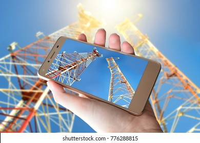 A smartphone in the hand against the sky and a telecommunications antenna. Telecommunication towers. The concept of telecommunications. The concept of communication technology for smartphones.