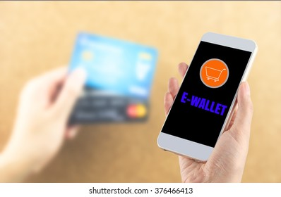 smartphone in hand with blurred credit card in hand word e-wallet