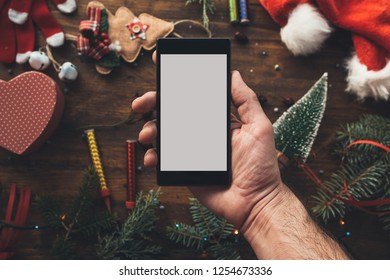 Smartphone in hand for Christmas season mock up with festive holiday decoration in background.