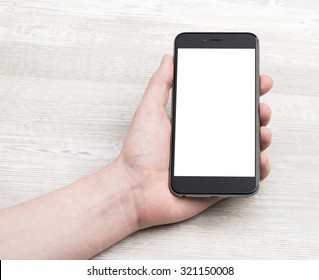Smartphone in hand, closeup on a light table