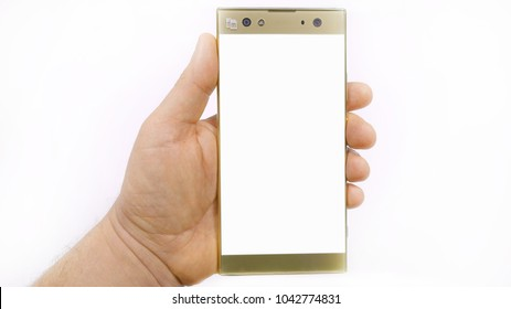 Smartphone in hand, man's hand holds a glass mobile phone  of gold color on a white background.
