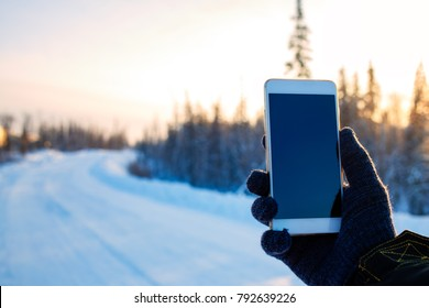 Smartphone in hand on the background winter snow-covered road in the woods