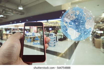 Smartphone in hand with shopping symbol and world global connect concept on blurred shopping mall background.