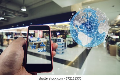 Smartphone in hand with shopping symbol and world global connect in shopping online concept on blurred shopping mall background.