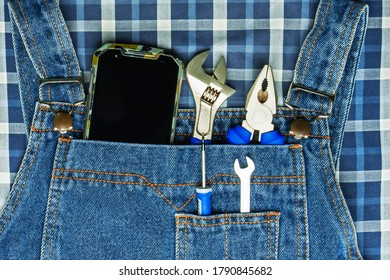 smartphone and hand tools are in the pocket of denim overalls.