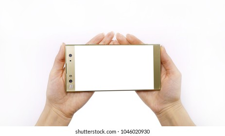 Smartphone in hand, woman's hand holds a glass mobile phone of gold color on a white background.