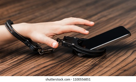 The smartphone is handcuffed in the hand of a little boy. a symbol of abuse of technology. High resolution.