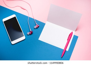 Smartphone, headphones and blank white sheet of paper on a pink and blue background.