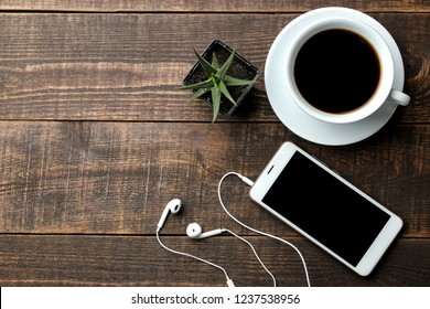 Smartphone with headphones and a cup with coffee on a brown wooden table. view from above