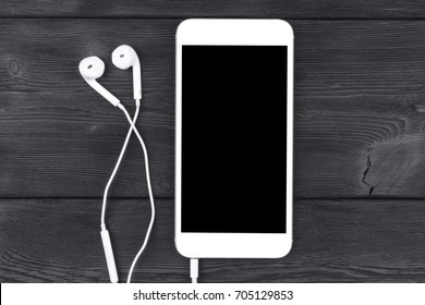 Smartphone with headphones on black wooden table. Smartphone with solated screen. Empty space for text. Copy space. Smartphone blank screen. Smartphone mock up and earphone.
