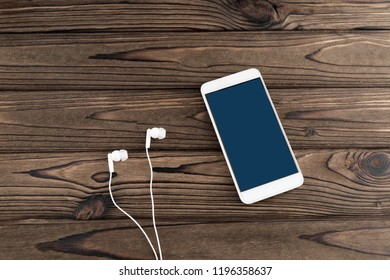 Smartphone with headphones on the wooden table background. Internet, music, entertainment.