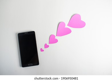 Smartphone and hearts paper on  White background. Valentine or Sending love through social networks.