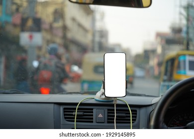 a smartphone held on a dashboard of a cab taxi with mockup white screen for navigation