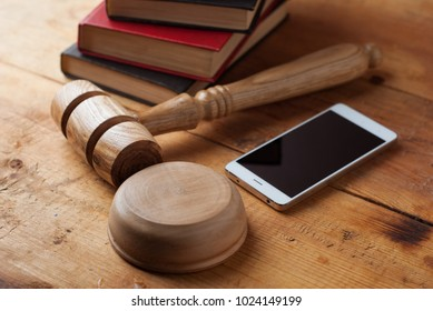smartphone, the judge's gavel on wooden background. Digital gadget. Illegal access to computer information,distribution of malicious programs. Violation of the secrecy of correspondence
