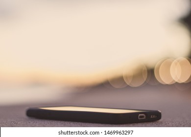 Smartphone laying down with a blurry bokeh background