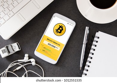 Smartphone is laying on the desk with cryptocurrency wallet application. Interface created in graphic program