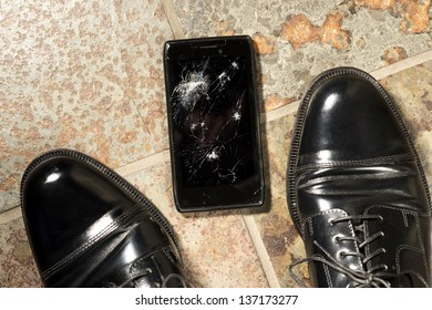 A smartphone lies broken between the shoes of its owner just after being dropped.