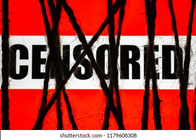 """Smartphone lying on a table in the dark, tightly wrapped and tied with coarse jute rope bondage lies with a glowing screen with a red text """"censored"""". Concept of censorship. Internet restricted access"""