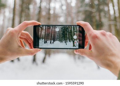 Smartphone in male hands in the winter forest. Sunny winter day.  Man holding mobile smart phone and taking photo, cellphone over blurred snowy forest.