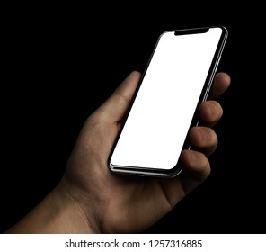 Smartphone in Man hand blank screen isolated on black background for night, dark mode applications template mockup