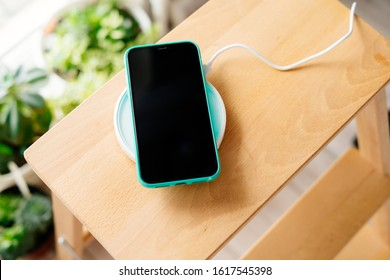 Smartphone in mint silicone case is charged from a wireless charger. The mobile phone is charged on a wooden nightstand or shelf.