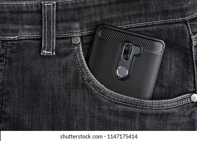 A smartphone (mobile phone) with two cameras in the case lies in the front pocket of black jeans