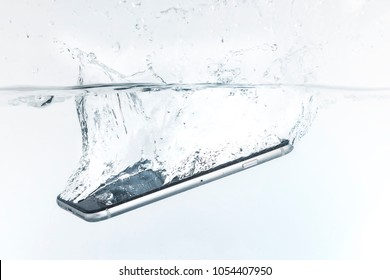 smartphone or mobile that falls in the water with splashes around and white background, concept closeup smartphone of waterproof