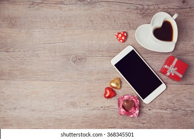 Smartphone mock up flat lay for Valentine's day with coffee cup and chocolate. View from above